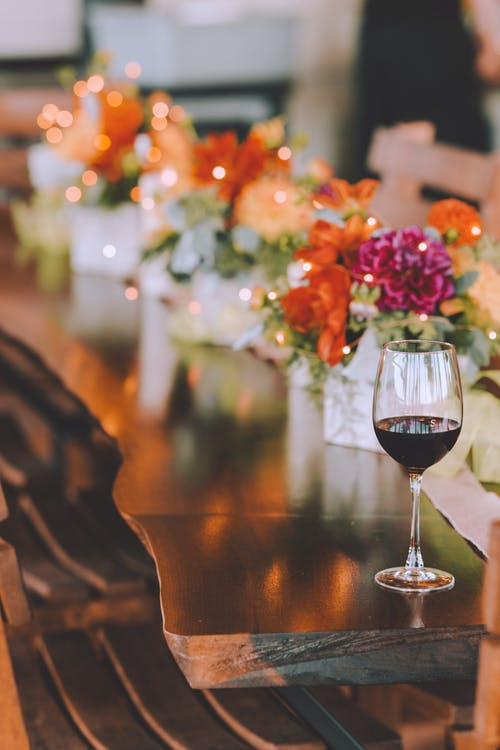 Glass of red wine placed on brown wooden shiny table decorated with bouquets of fresh colorful flowers amidst glowing garland