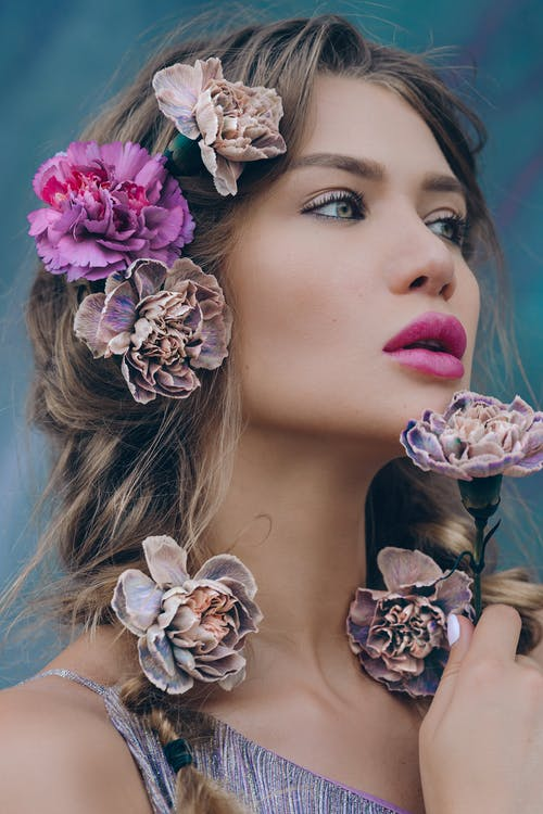 Gorgeous young woman with colorful flowers in hair
