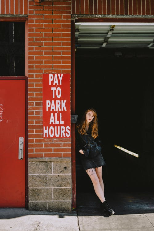 Confident young woman leaning on entrance of parking