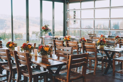 Wooden tables and chairs decorated with bouquets of colorful flowers in cozy modern cafeteria