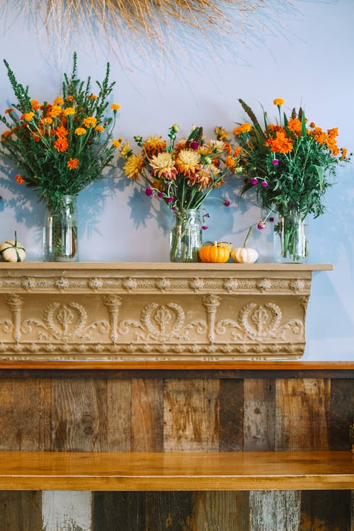 Bouquets of colorful flowers in glass vases on ornate shelf decorated with relief