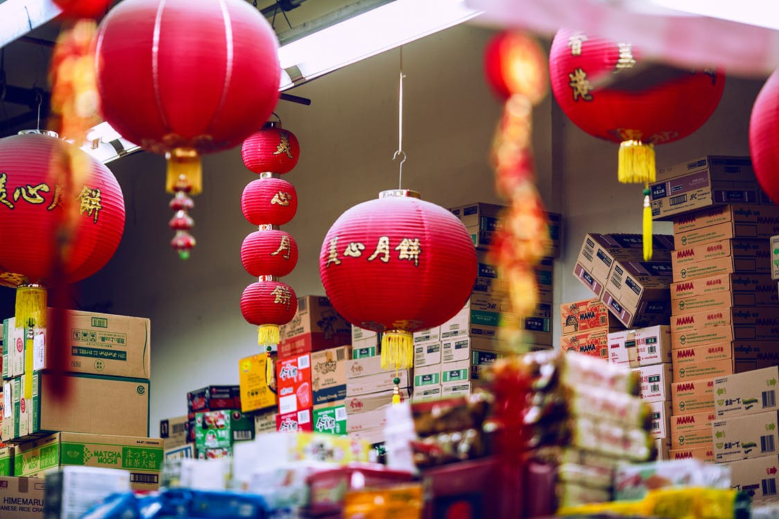 Colorful Chinese lanterns hanging amidst carton boxes with food in storage on market