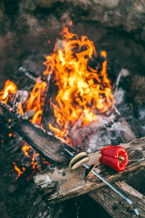 From above of metal skewer with eggplant hats near red pepper on burnt plank above bonfire