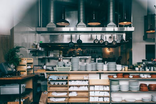 Interior of kitchen in modern restaurant with piles of plates and other different assorted utensils