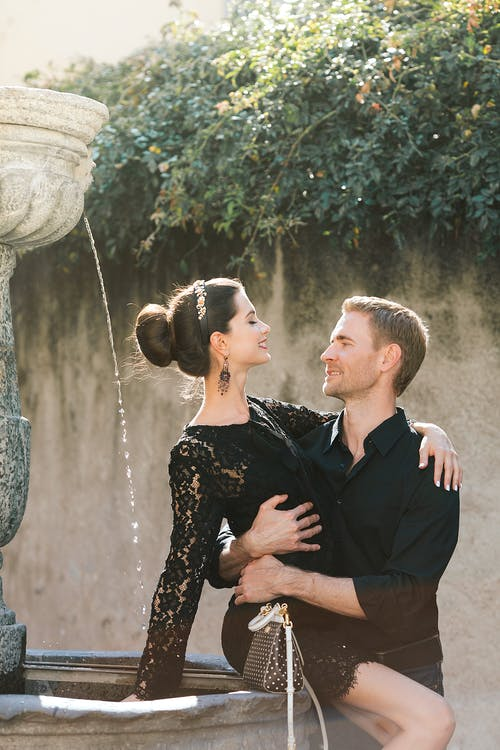 Cheerful man embracing elegant girlfriend with hair bun on fountain while looking at each other in back lit