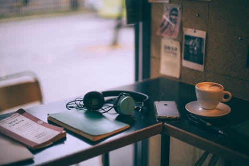 Headset on copybook near book and cellphone on cafeteria table with delicious coffee in cup
