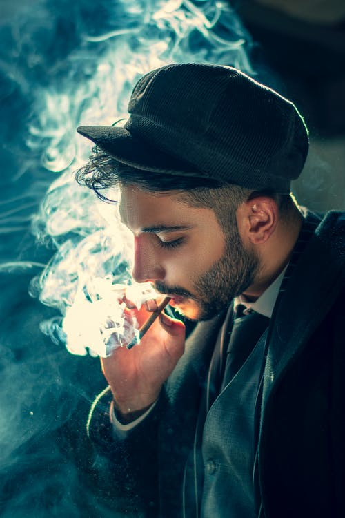 Man Smoking Cigarette Wearing Black Hat