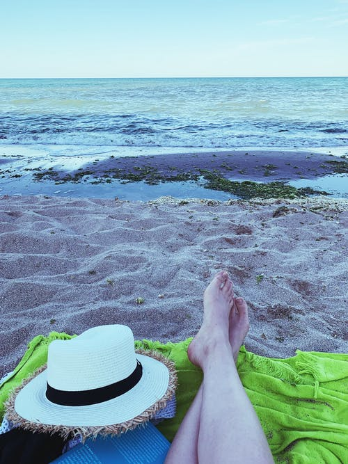 Crop person on blanket near sea