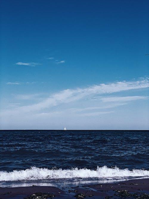 Picturesque scenery of foamy waves rolling near wet sandy coast under blue sky in daylight