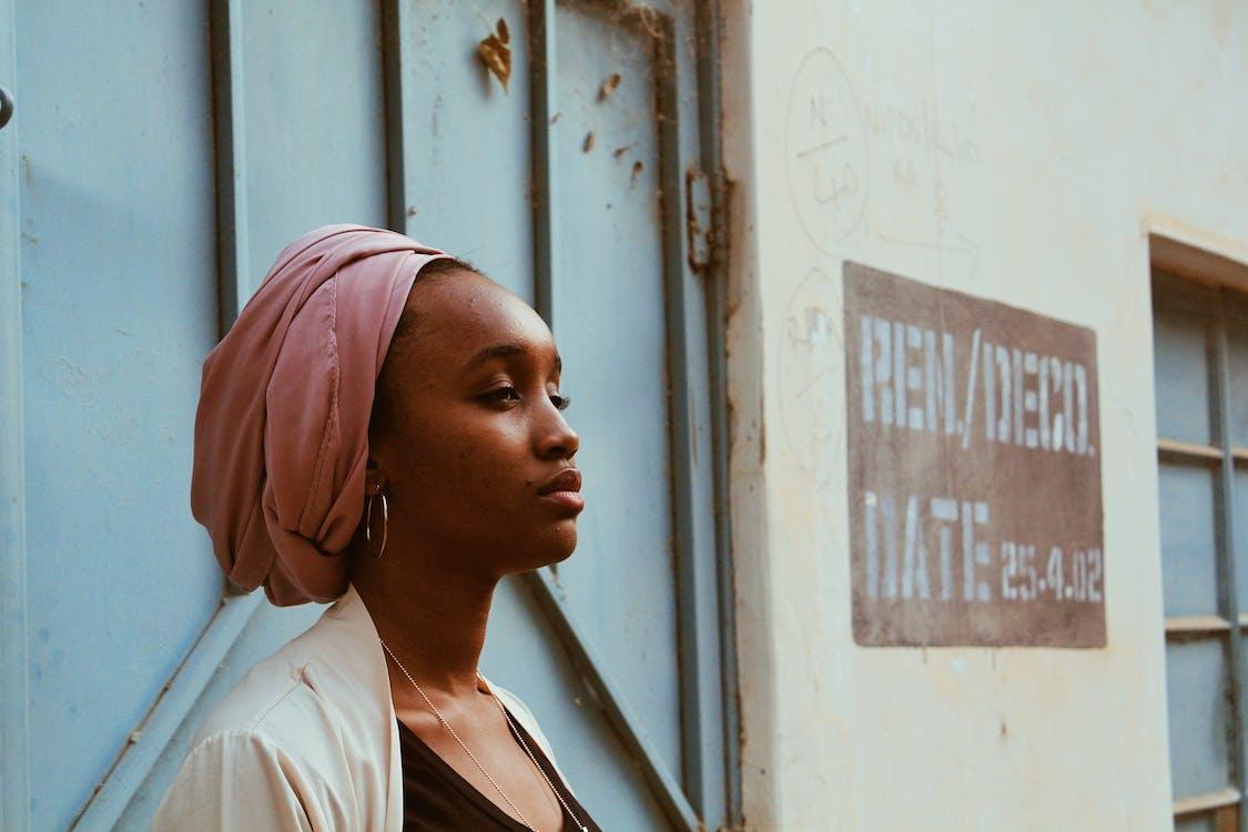 Black woman in headscarf next to old massive door