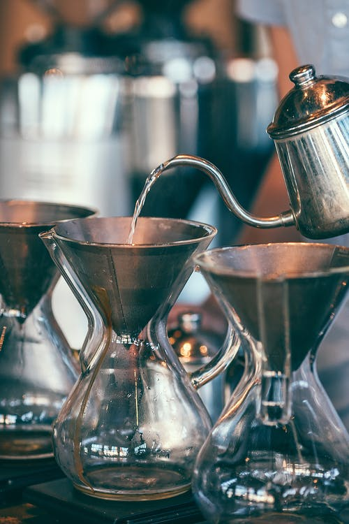 Crop barista with pour over coffee maker and carafes
