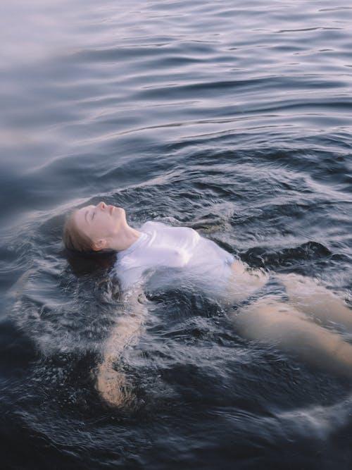 Frau Im Weißen Hemd, Das Auf Körper Des Wassers Liegt