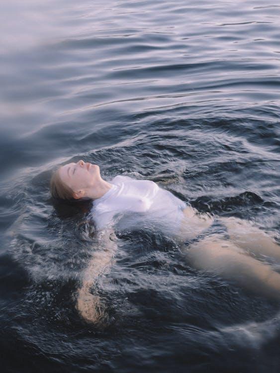 Vrouw In Wit Overhemd Liggend Op Het Waterlichaam