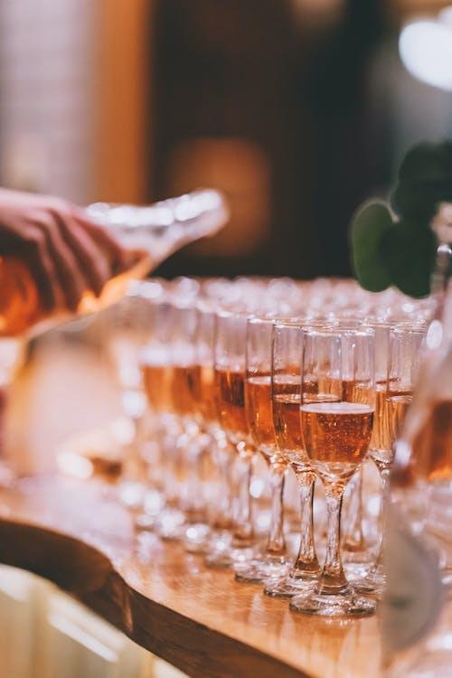 Crop bartender serving champagne in glasses in restaurant