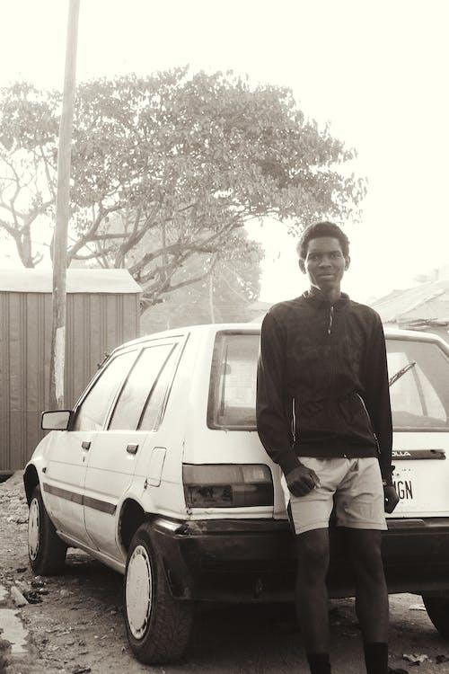 Pensive black man near old car