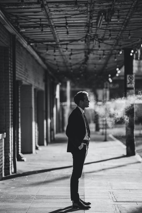 Black and white side view of male entrepreneur in formal suit with hand in pocket looking forward between haze and building on pathway