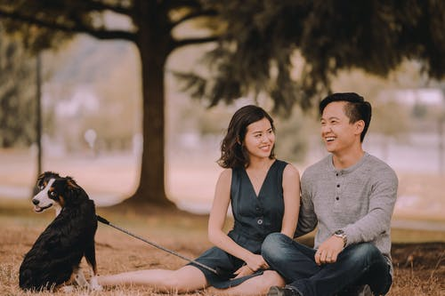 Glad ethnic couple with Bernese Mountain Dog on leash sitting on grass while spending time together on weekend