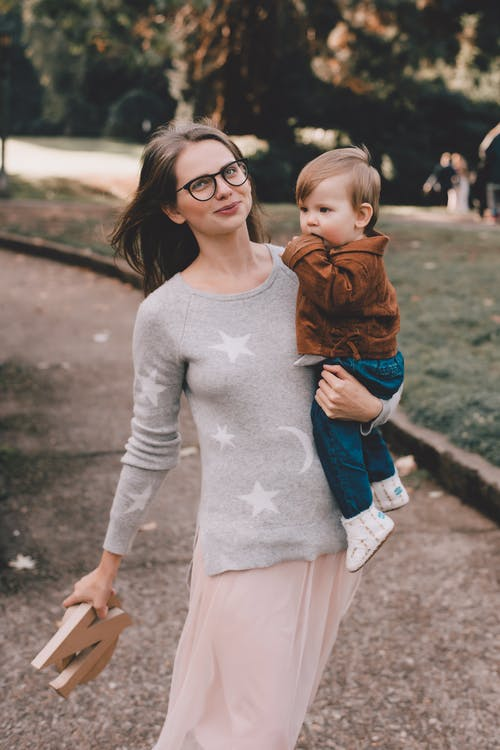Happy mother in casual clothes and eyeglasses holding toddler on arms with wooden letters in hand walking on pathway in park