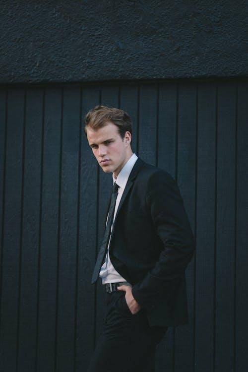 Man in Black Suit Jacket Standing Near Blue Wall