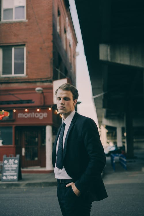 Confident young man in formal suit standing on city street with closed eyes and keeping hands in pocket
