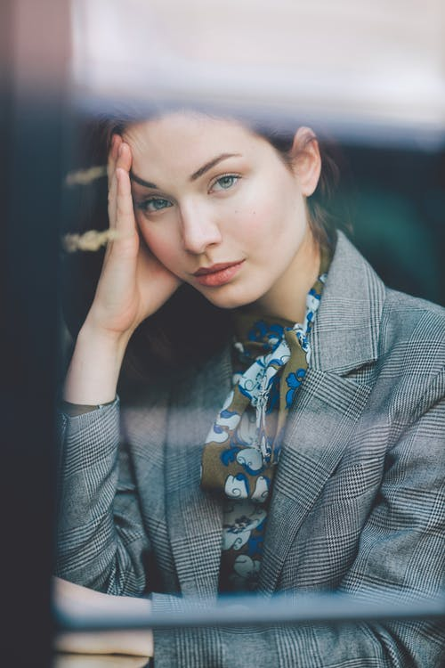 Through glass of young contemplative female in elegant suit leaning on hand and looking at camera while sitting at table in cafe