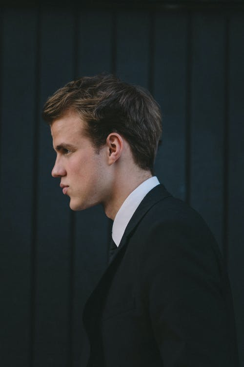 Side view of young handsome man in classic suit near black wooden wall on street