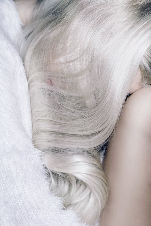 Shiny and wavy long blond hair covering face of sleeping young slender woman