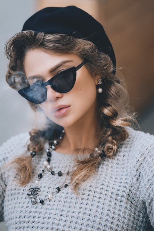 Young elegant woman with stylish sunglasses beret and accessories exhaling smoke looking at camera