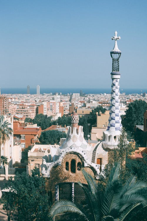 Surrealistic architecture of towers and gardens against modern cityscape in sunny summer day in Spain