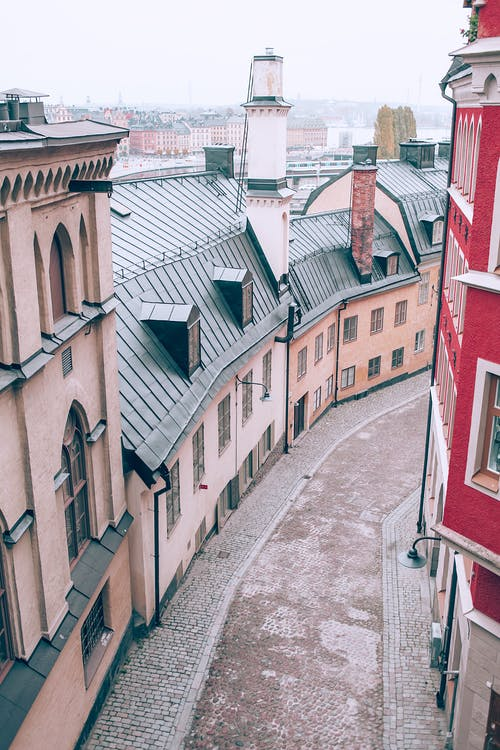 From above of old stone residential buildings located on narrow paved street in European city