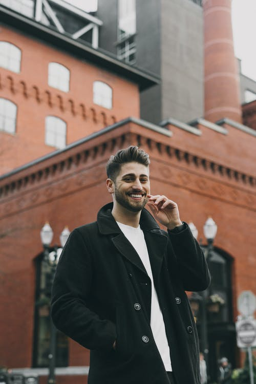 Cheerful handsome man in coat standing outside modern building