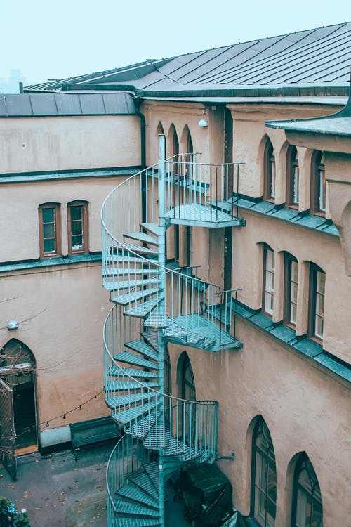 Exterior of old apartment building with outdoor spiral stairway and windows of different shapes