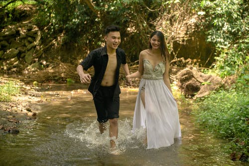 Cheerful ethnic couple holding hands while running towards camera in splashing water in sunny forest