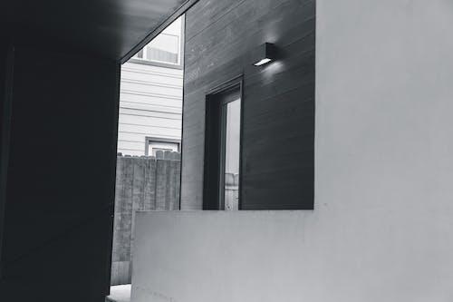 Wall mounted lamp near door in yard of modern house
