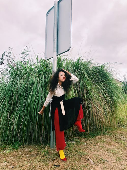 Woman in Black Long Sleeve Shirt and Red Skirt Standing on Green Grass Field