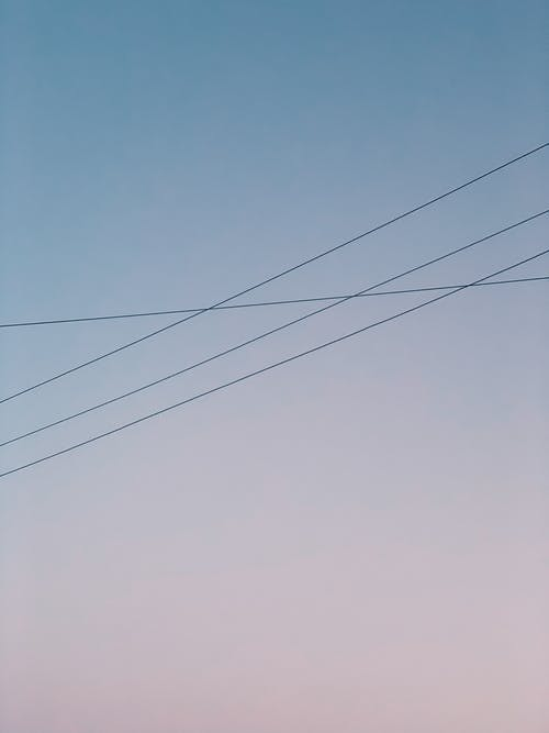 From below of thin electricity wires against blue and soft pink sky at sunset