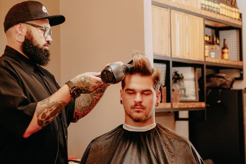 Barber drying hair of male client in salon