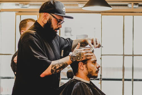 Side view of young tattooed bearded male hairdresser in casual clothes and eyeglasses cutting hair of client in modern barbershop