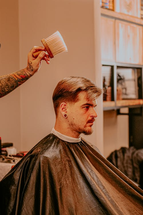 Anonymous barber with brush after haircut for male client