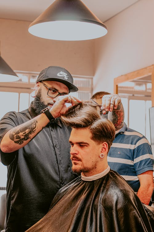 Bearded barber cutting doing haircut to male client in salon