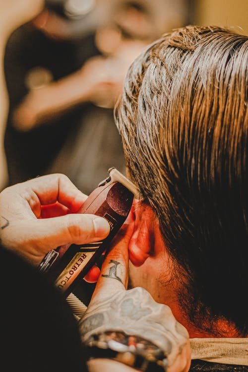 Crop tattooed barber trimming hair of anonymous male client in modern beauty salon