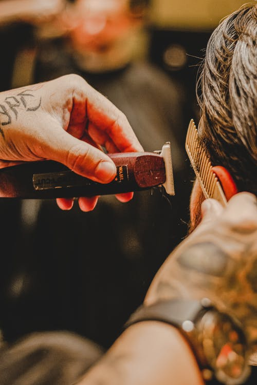 Crop faceless tattooed barber combing hair of anonymous client while using trimmer in salon