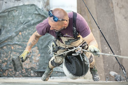 From above of man in safety harness hanging above ground and smoothing wall skim coat with liquid plaster using coarse brush