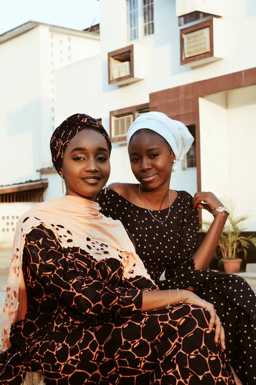 Cheerful African female friends in stylish clothing looking at camera with smile while lounging on street near simple residential building