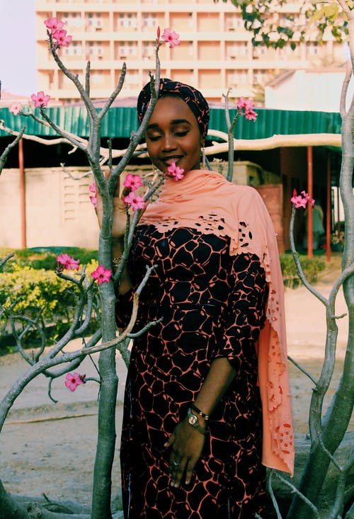 Black woman smelling flower on branch of tree