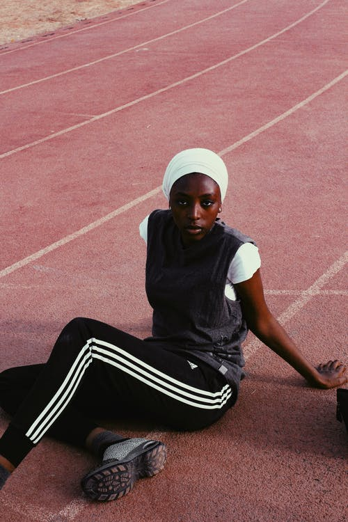 Full body of young pensive African American female runner in sportswear resting on dark red track in daytime