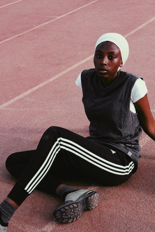 Pensive black runner in hat on sportsground