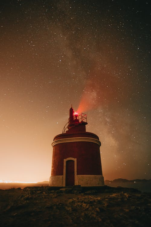 Low angle of red light glowing on tower of lighthouse against night sky with milky way and stars in twilight