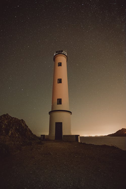 Low angle of lighthouse tower with small windows located on pathway against starry sky in night time in nature outside