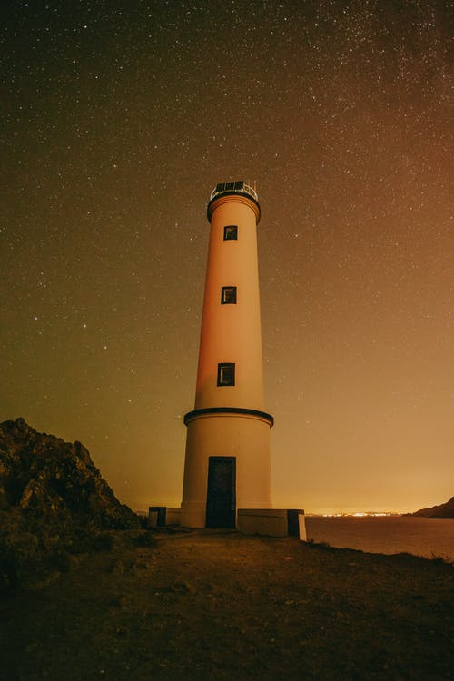 Low angle of white lighthouse tower located near rocky mountain and barriers against stars glowing on night sky in summer